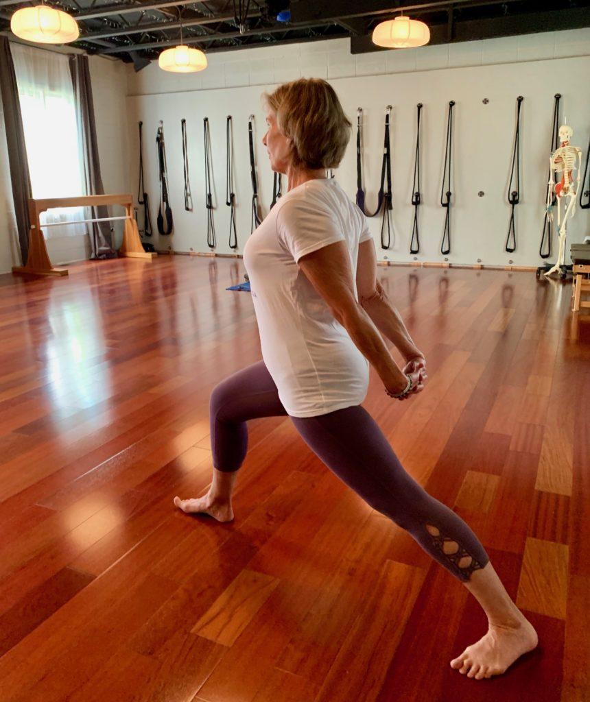 Yoga teacher strikes pose in studio